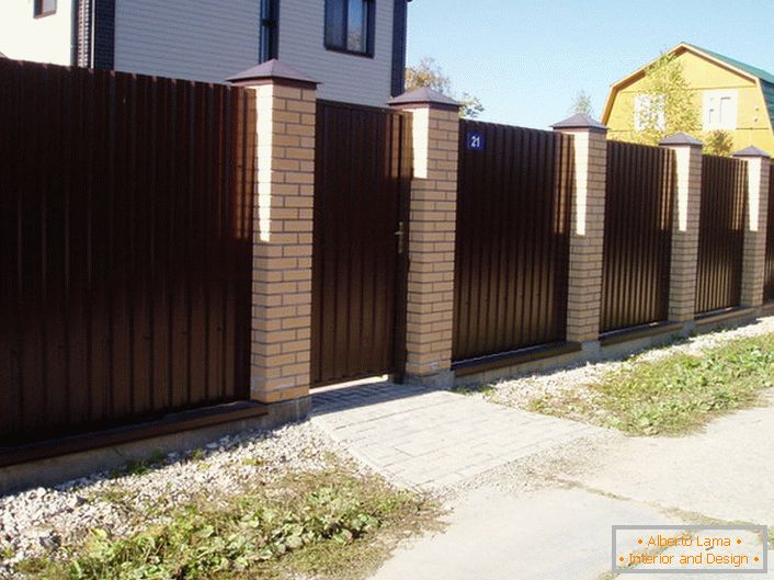 Modular fence is dark brown with a brick finish - a classic of the genre, if we talk about the design of suburban areas.
