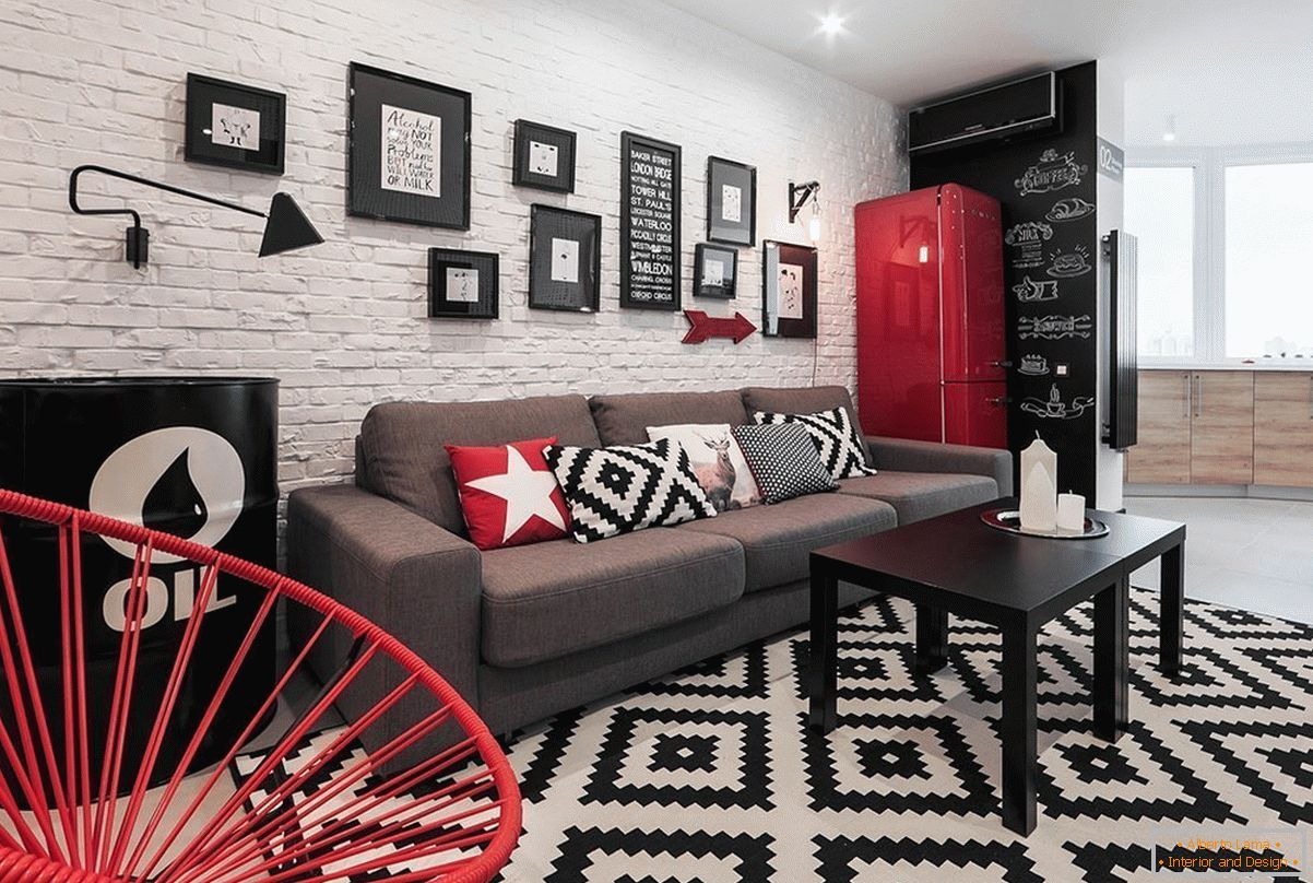 Red decor elements in a black and white studio apartment