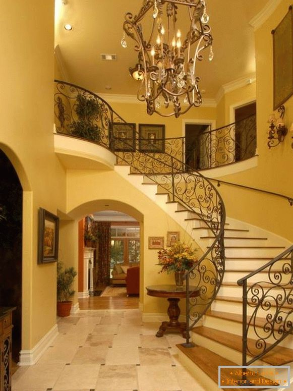 Large forged chandelier in front of stairs in the hall