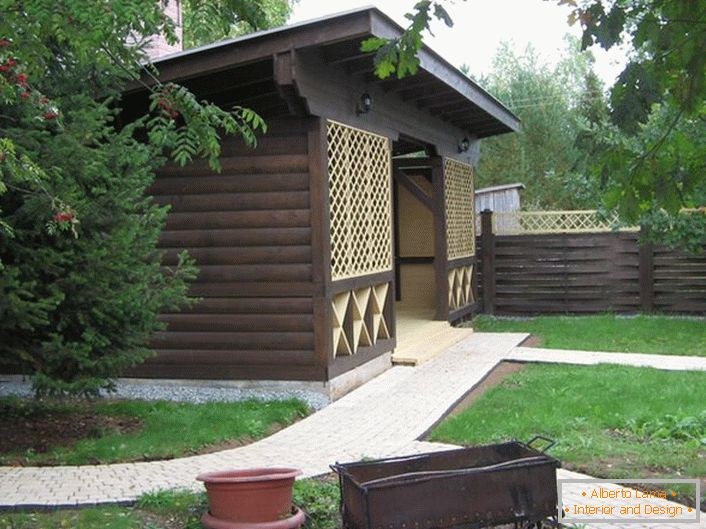 A dark gazebo made of wood in the style of a chalet is a popular choice for modern suburban real estate owners.
