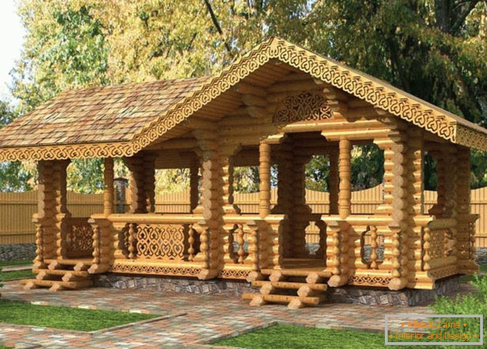 A fairy-tale gazebo in the style of a chalet is built of a light beam. To the gazebo lead the paths of granite tiles.