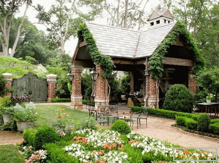 The elegant simplicity of an open gazebo in the style of a chalet looks organically in a luxurious, cozy garden.