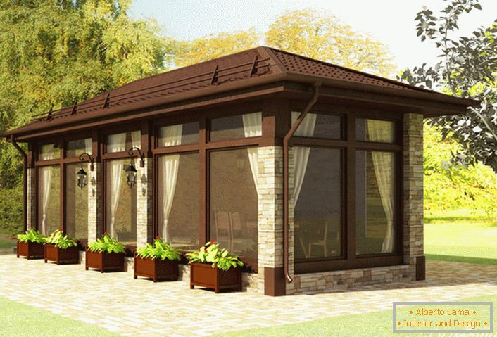 A modern gazebo in the style of the chalet is finished with natural stone. A creative solution for the design of the landscape structure - pots with greens.