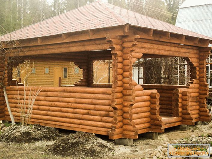 A wooden frame is the most suitable material for making an arbor for an infield in the style of a chalet. The roof made of terracotta tiles looks organically on the background of an aged tree.