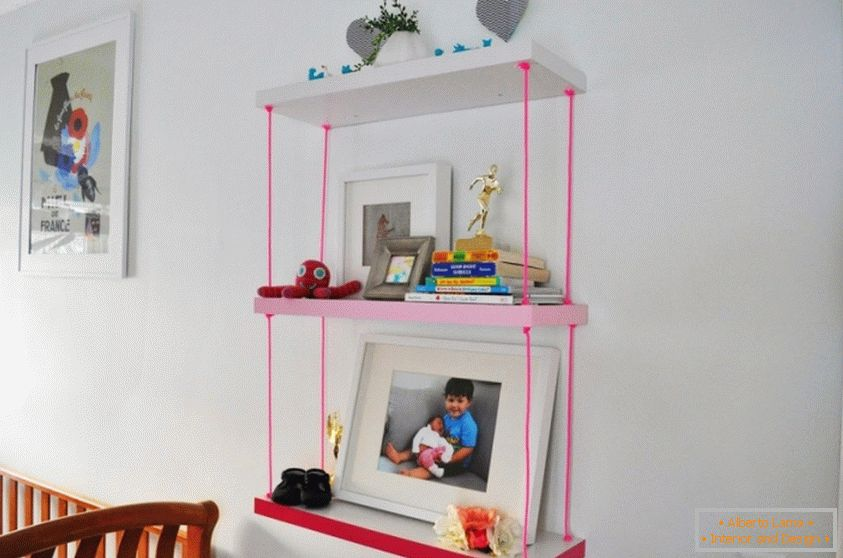 A bookshelf for a children's room with pink ropes