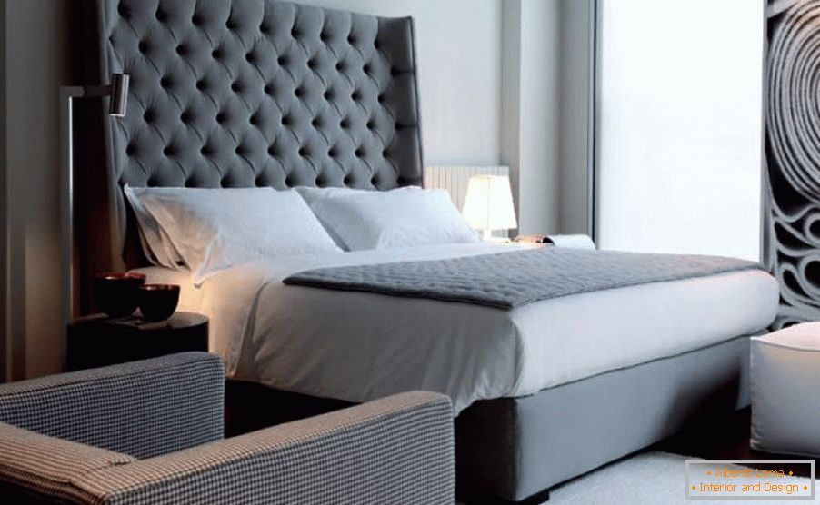 A large bed with a high headboard