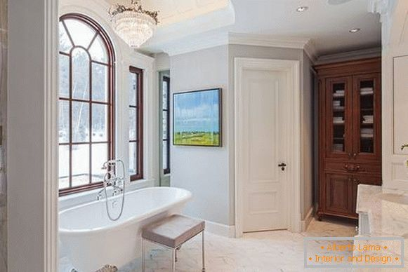 Light doors in the interior of the bathroom with white tiles