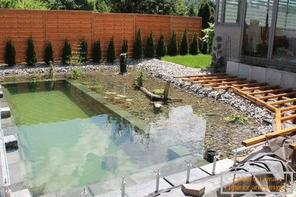 Shallow pond or pool on the plot with your own hands photo