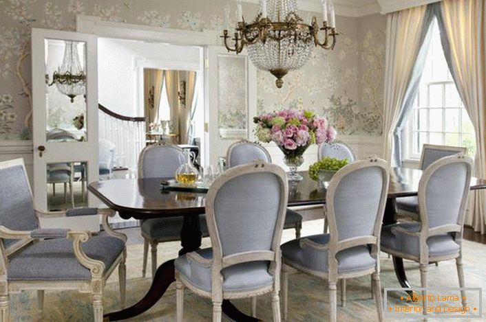 The dining room in the Neoclassic style is decorated in pale blue and light gray colors. Flower wallpaper gently look in combination with white high plinths.