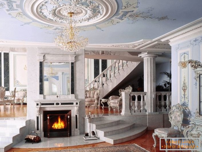The hall with a fireplace in the neoclassic style is notable for the color scheme chosen for decoration. A gentle blue and white shade harmoniously combined in a single composition.