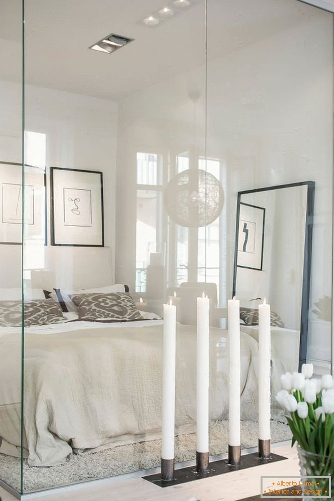 Bedroom behind the glass studio apartments in Scandinavian style