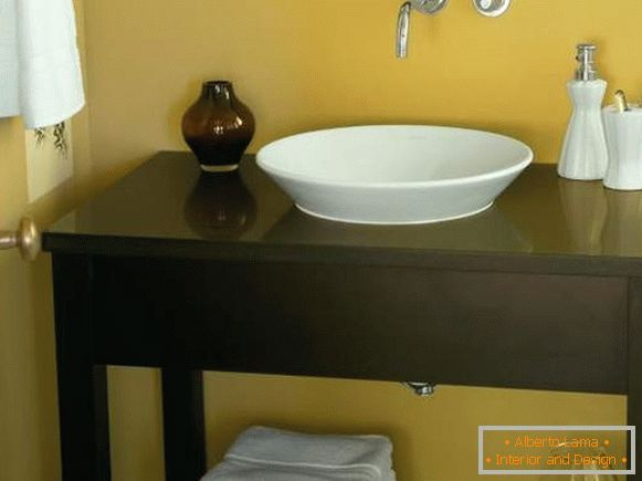 A table of a curbstone under a sink in a bathroom the hands