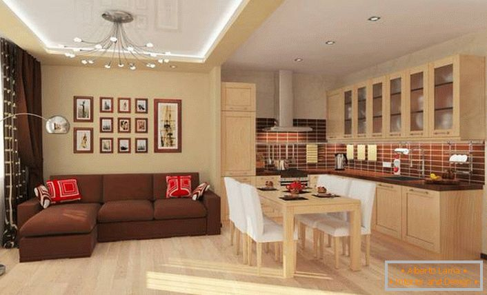 The dining area separates the kitchen from the living room. Functional variant of interior design in a spacious one-room apartment.