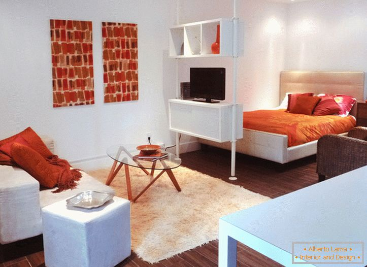 Interior of a white studio apartment with orange accents